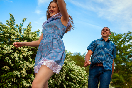 Photo for Couple running in spring blooming park. Young man and woman having fun at sunset. - Royalty Free Image