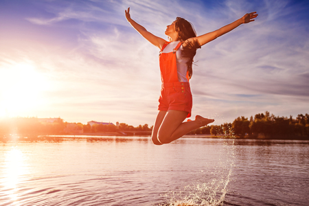Photo for Happy and free young woman jumping and raising arms on river bank. Freedom. Active lifestyle. Summer holidays - Royalty Free Image