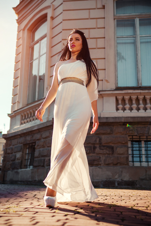 Photo for Beautiful woman walking in white wedding dress outdoors. One shoulder dress with accessories, jewellery and heels. Fashion concept - Royalty Free Image