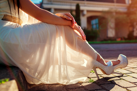 Photo for Stylish woman wearing high heeled shoes and white dress outdoors. Beauty fashion. Girl sitting with hands put on legs - Royalty Free Image