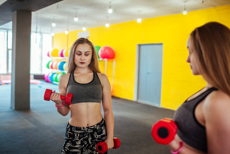 Photo for Shot of young woman exercising with dumbbells at the gym. Muscular female training in front of the mirror in the morning. - Royalty Free Image