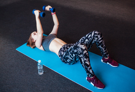 Photo for Shot of young woman exercising with dumbbells at the gym. Muscular female training on exercise mat in the morning - Royalty Free Image