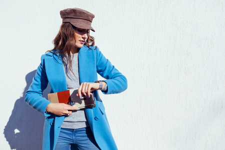 Foto de Young woman looking on watch, holding stylish handbag and wearing trendy blue coat and cap. Spring female clothes and accessories. Fashion - Imagen libre de derechos