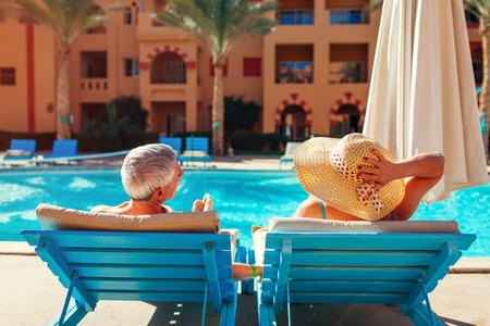 Foto de Senior family couple relaxing by swimming pool lying on chaise-longues. People enjoying summer vacation. - Imagen libre de derechos