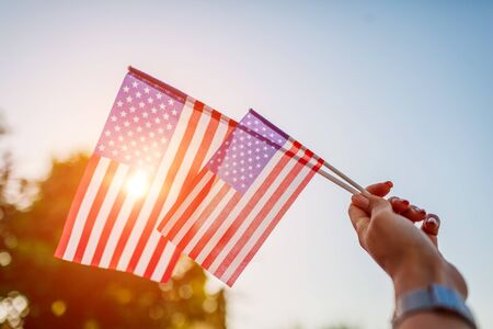 Photo for Woman holding USA flag against the blue sky. Celebrating Independence Day of America - Royalty Free Image