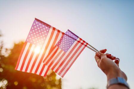 Foto de Woman holding USA flag against the blue sky. Celebrating Independence Day of America - Imagen libre de derechos