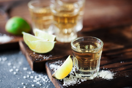 Photo for Tequila golden with lime and sea salt decorated with blackberry and mint on the dark background - Royalty Free Image