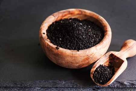 Photo pour Black cumin or nigella sativa or kalonji seeds in bowl with spoon on black slate background, selective focus - image libre de droit