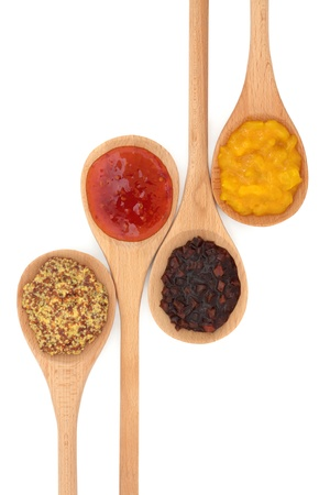Wholegrain mustard, chili sauce, sweet vegetable pickle and piccalilli, in wooden spoons isolated over white background.