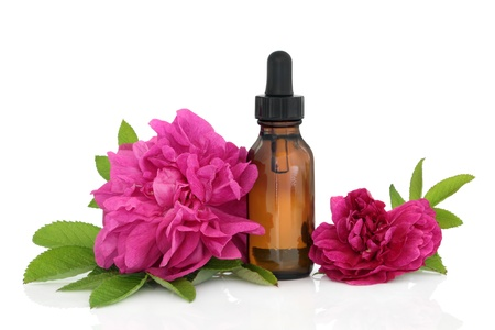 Photo for Rose flowers with aromatherapy essential oil glass bottle isolated over white background. - Royalty Free Image