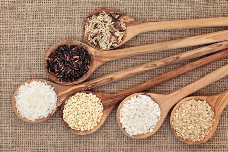 Foto de Rice varieties in olive wood spoons over hessian background    - Imagen libre de derechos
