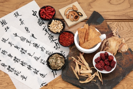 Photo for Traditional chinese herbal medicine selection with mandarin calligraphy on rice paper over oak  Translation describes the medicinal functions to increase the bodys ability to maintain body and spirit health and balance energy  - Royalty Free Image