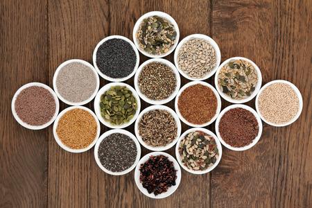 Photo pour Large seed superfood selection in white porcelain bowls over oak background  - image libre de droit