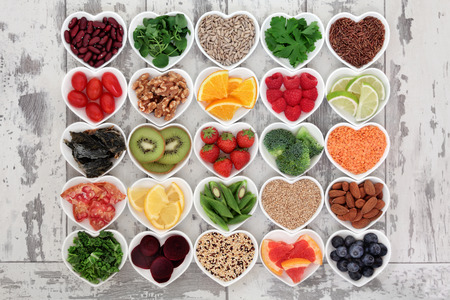 Foto de Diet detox super food selection in heart shaped porcelain bowls over distressed wooden background. - Imagen libre de derechos