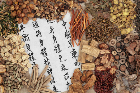 Foto de Chinese herb selection with calligraphy script. Translation describes chinese herbal medicine as increasing the bodys ability to maintain body and spirit health and balance energy. - Imagen libre de derechos