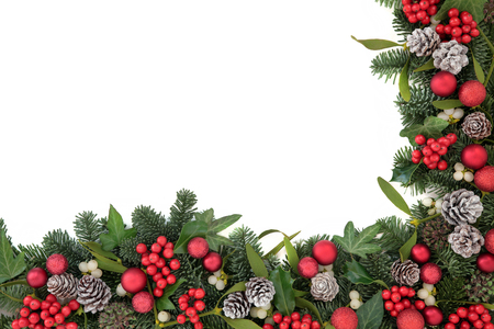 Photo pour Christmas background border with bauble decorations, holly, ivy, mistletoe, pine cones and blue spruce fir over white. - image libre de droit