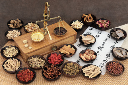 Foto de Chinese medicine ingredients with scales and calligraphy on rice paper. Translation read as chinese herbal medicine as increasing the bodys ability to maintain body and spirit health and balance energy. - Imagen libre de derechos