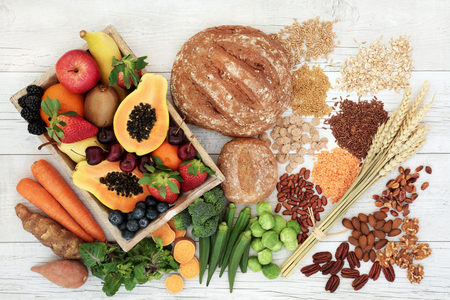Photo for Healthy high fibre diet food concept with legumes, fruit, vegetables, wholegrain bread, cereals, grains, nuts and seeds. Super foods high in antioxidants, anthocyanins, omega 3 and vitamins. Rustic wood background, top view. - Royalty Free Image