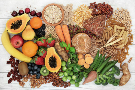 Photo for Food with high fiber content for a healthy diet with fruit, vegetables, whole wheat bread, pasta, nuts, legumes, grains and cereals. High in antioxidants, anthocyanins, vitamins and omega 3 fatty acid. Rustic background top view. - Royalty Free Image