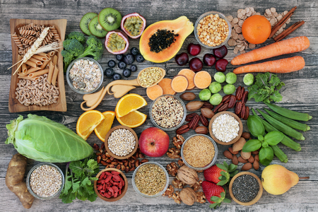 Photo for High dietary fiber health food concept with fruit, vegetables, whole wheat pasta, legumes, cereals, nuts and seeds  with foods high in omega 3, antioxidants, anthocyanins, smart carbohydrates and vitamins. Rustic background top View. - Royalty Free Image
