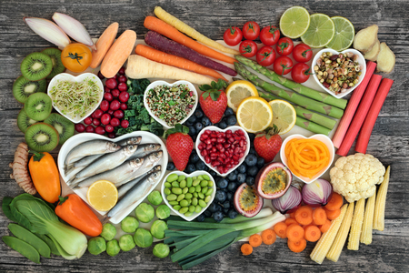 Photo pour Healthy super food concept with fresh fish, vegetables and fruit in heart shaped dishes and loose, top view on rustic background. Health food high in omega 3, antioxidants, anthocyanins, minerals, vitamins and fiber. - image libre de droit