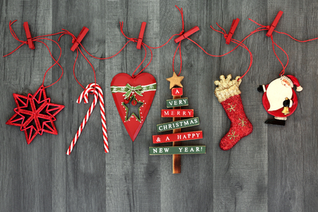 Foto de Christmas tree retro bauble decorations hanging on a red string line with pegs on rustic wood background. Festive Christmas card for the holiday season. - Imagen libre de derechos