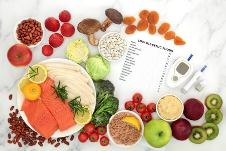 Foto de Low glycemic food for diabetics with blood sugar testing equipment & lancing device. Health foods below 55 on the GI index, high in vitamins, minerals, anthocyanins, antioxidants, smart carbs & omega 3 fatty acids. - Imagen libre de derechos