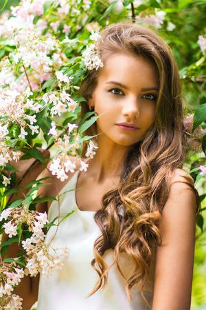 Portrait of beautiful girl near flowering branches in spring garden
