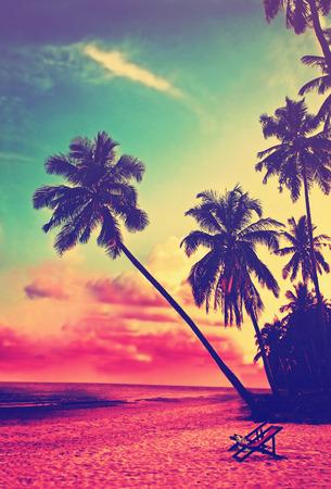 Foto de Beautiful tropical beach with silhouettes of palm trees at sunset - Imagen libre de derechos