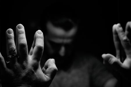 Foto de Man in despair with raised hands and bowed hand, monochromatic image in a low light room looking in front of mirror - Imagen libre de derechos