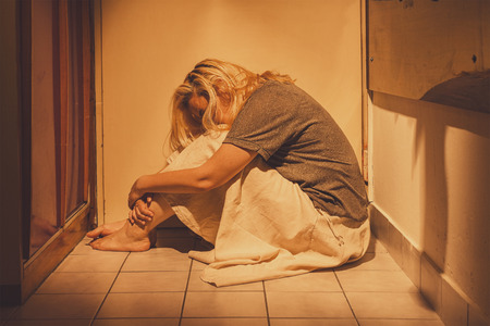 Photo for Sad, depressed and lonely woman sitting in a corner on a floor tiles, in a skirt, barefoot with a long blond hair - Royalty Free Image