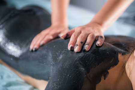 Foto de Mud massage with woman hands on body. - Imagen libre de derechos