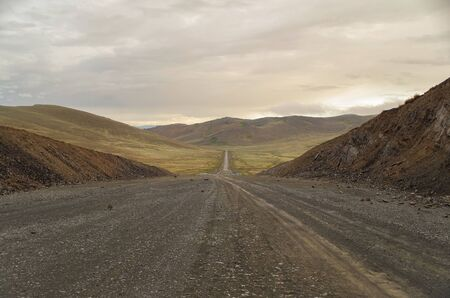 Photo pour Mongolian Altai. Dirt road and mountain valley at evening. Road from Russia, near Ulaanbaishint Check Point. Nature and travel. Mongolia, Bayan-Olgii Province - image libre de droit
