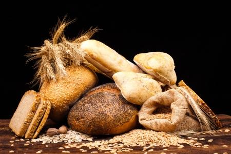 Foto de assortment of baked bread on wood table and black background - Imagen libre de derechos