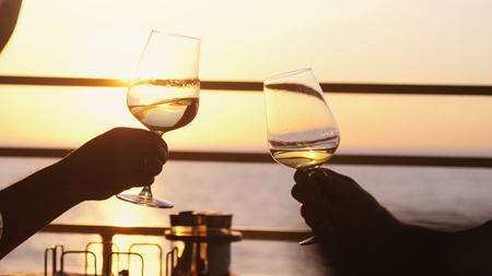 Photo for People holding glass of wine, making a toast over sunset. Party outdoors. Enjoying time together. - Royalty Free Image