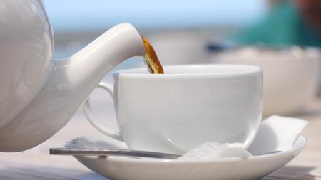 Foto de White teapot pouring tea into cup in beach cafe by the sea with sunlight. - Imagen libre de derechos