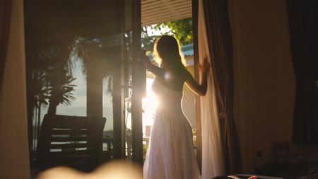 Foto de Beautiful brunette girl stands in the doorway in the early morning during sunrise with lens flare effects - Imagen libre de derechos