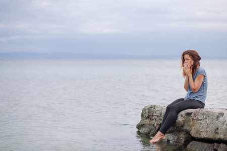 Photo pour Woman alone and depressed at seaside - image libre de droit