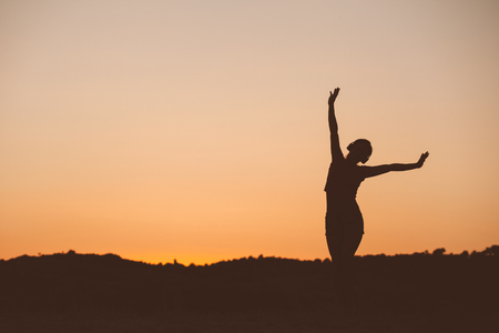Photo pour Silhouette of woman listening the music on sunset fiery sky - image libre de droit