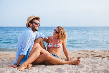 Photo for Young couple in love lying on the beach enjoying - Royalty Free Image