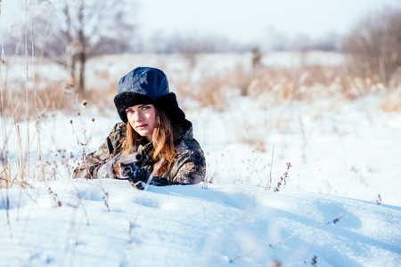 Foto de A beautiful girl hunter in camouflage suit with binoculars and a gun lies in cover in anticipation of prey, preparing to shoot. photo concept of hunting, people, weapons - Imagen libre de derechos