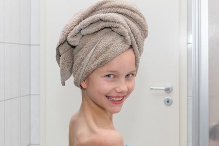 Foto de A girl is standing in the bathroom, wrapping the towel in a turban, portrait - Imagen libre de derechos