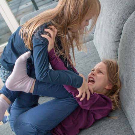 Photo pour A 7- and a 9-year-old girl scream at each other and beat each other - image libre de droit