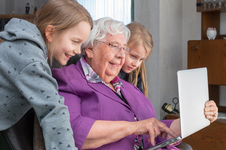 Photo for A 95 year old woman is holding a laptop  and showing her grandchildren something funny. She is sitting on a armchair in her living room and they are  looking at the screen - Royalty Free Image