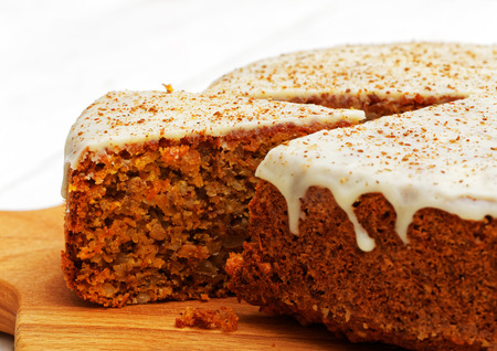 Foto de Closeup homemade sweet carrot cake with walnuts, cinnamon and white icing on white wooden table - Imagen libre de derechos