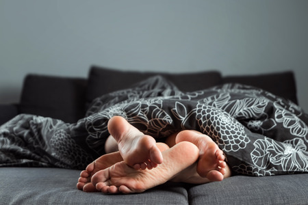 Foto de The legs, feet of a couple in love are sticking out from under the blanket. Valentine's Day or love story. Prelude in bed, sex, adult sites, love, relationships. - Imagen libre de derechos