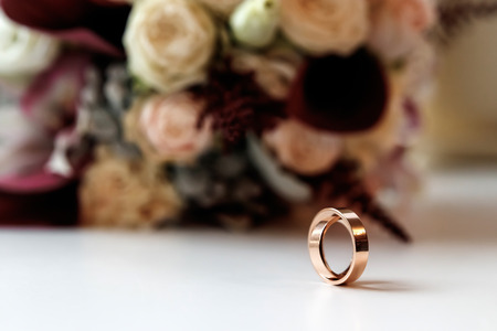 Photo pour A beautiful picture with wedding rings lies against the background of a bouquet of flowers - image libre de droit