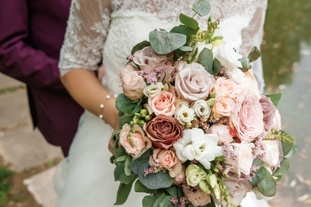 Photo pour Beautiful bride is holding a wedding colorful bouquet. Beauty of colored flowers. Close-up bunch of florets. Bridal accessories. Female decoration for girl. Details for marriage - image libre de droit