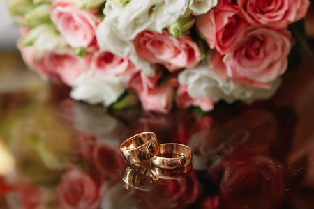 Photo pour Wedding rings with bridal bouquet lying on the morning of the bride. - image libre de droit