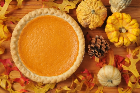 Photo for A whole sweet potato pie on an artistic set with autumn leaves, squash and gourds. - Royalty Free Image